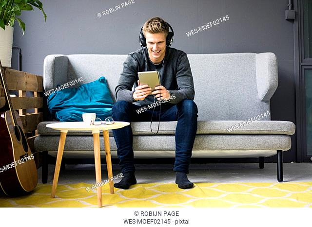 Smiling young man with guitar, tablet and headphones sitting on couch