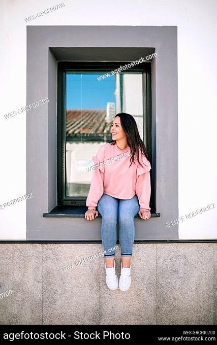 Beautiful woman looking away while sitting on window sill