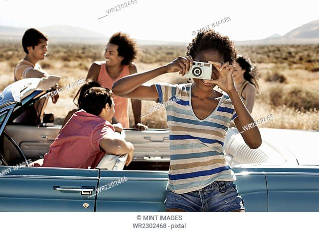 A group of friends by a pale blue convertible on the open road, on a flat plain surrounded by mountains, one holding a camera