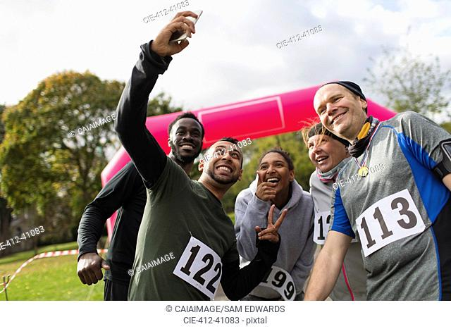 Friend runners taking selfie at charity run in park