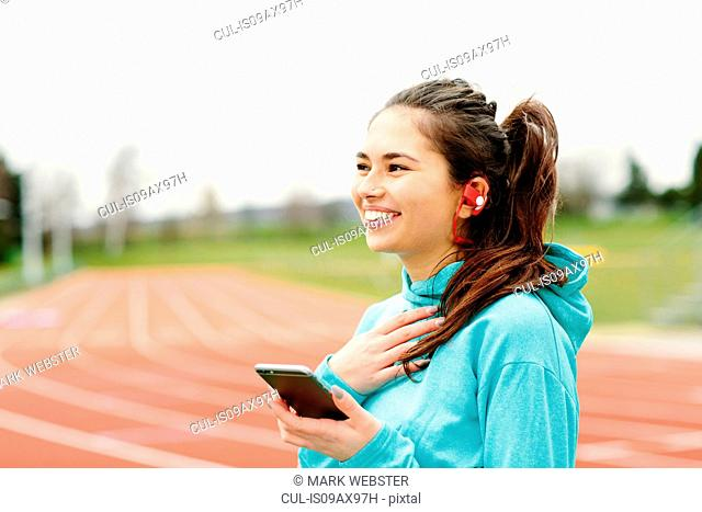 Young woman beside running track, holding smartphone, wearing earphones, smiling