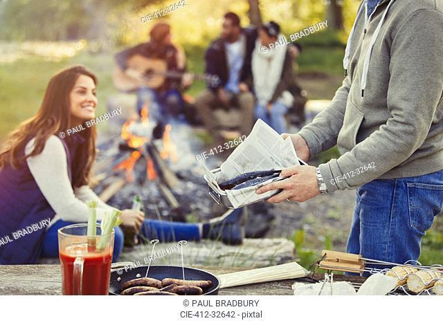 Man preparing hot dogs and fish at campfire