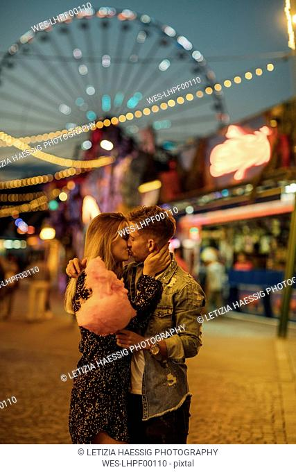 Romantic couple at a funfair eating candy floss