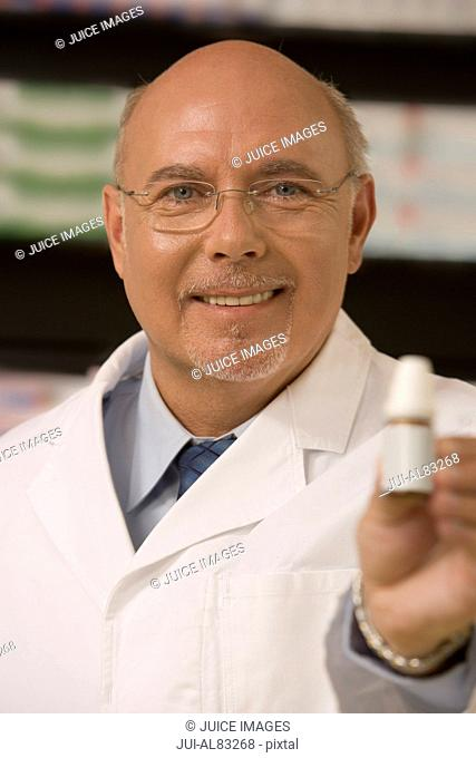 Male pharmacist smiling and holding medication