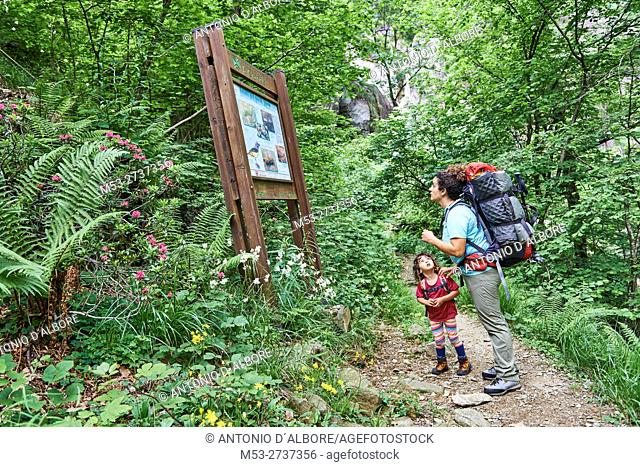 Mother and daughter on a mountain trail in Val Grande National Park. The mother read an information sign about the fauna of the forest