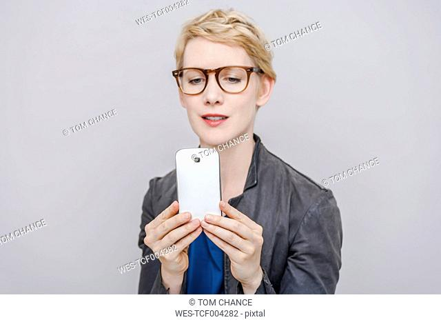 Blond woman taking a selfie with her smartphone