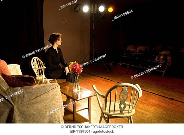 Woman sitting on a chair, stage, theatre, England, United Kingdom, Europe