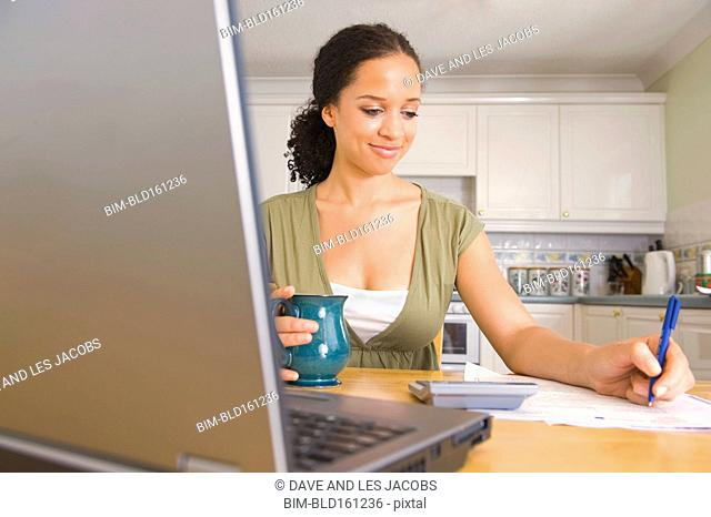 Mixed race woman paying bills at laptop in kitchen
