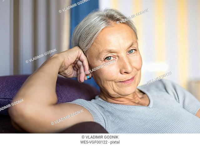 Portrait of smiling senior woman relaxing on the couch at home