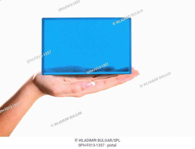 Person holding blue screen on palm of hand