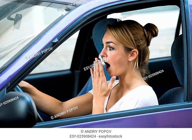 Shocked young woman with mouth open driving car