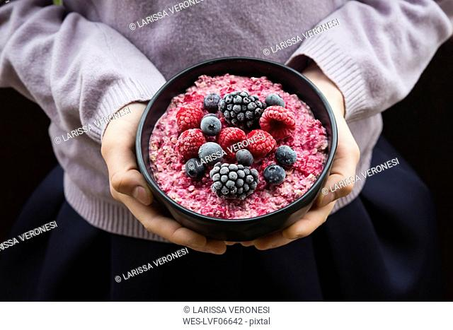 Girl holding bowl with overnight oats mit frozen berries