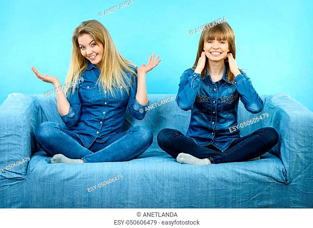 Friendship, human relations concept. Two happy women friends or sisters wearing jeans shirts sitting on sofa having fun