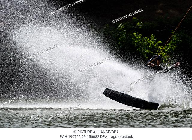 22 July 2019, North Rhine-Westphalia, Langenfeld: Water splashes as a wakeboarder on a water ski facility drives through a bend