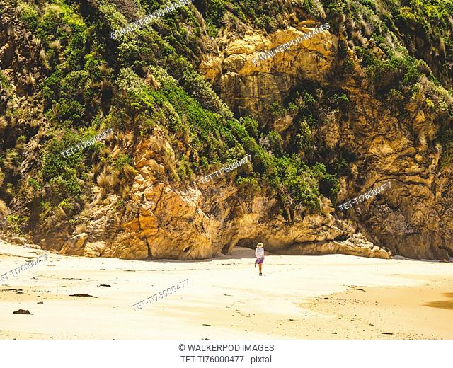Australia, New South Wales, Bermagui, Woman walking along beach
