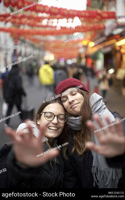 two women enjoying inner world together and keeping distance with hands between passersby in China Town in London, Great Britain