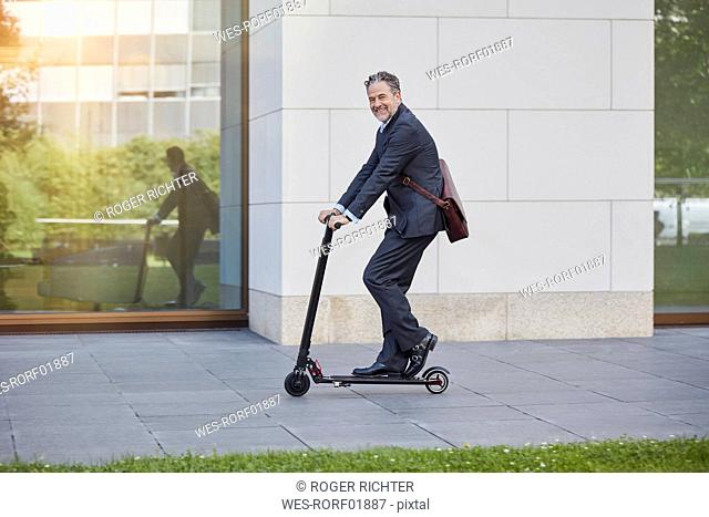 Businessman on e-scooter passing office building in the city