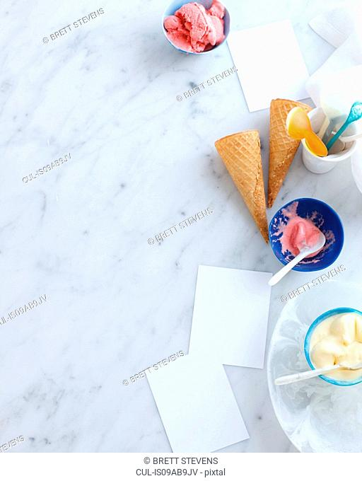 Still life with bowls of ice cream and cones