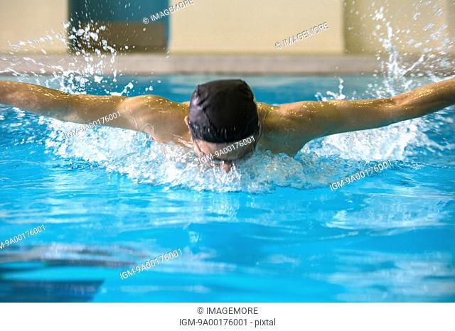 Young man swimming with arms outstretched