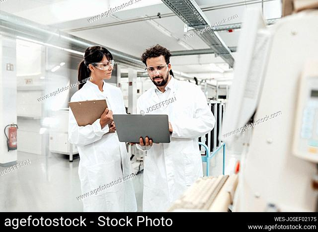 Female scientist looking at male colleague using laptop in laboratory