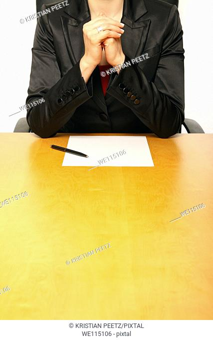 View of a business-woman sitting at the desk with a blank paper, gesturing