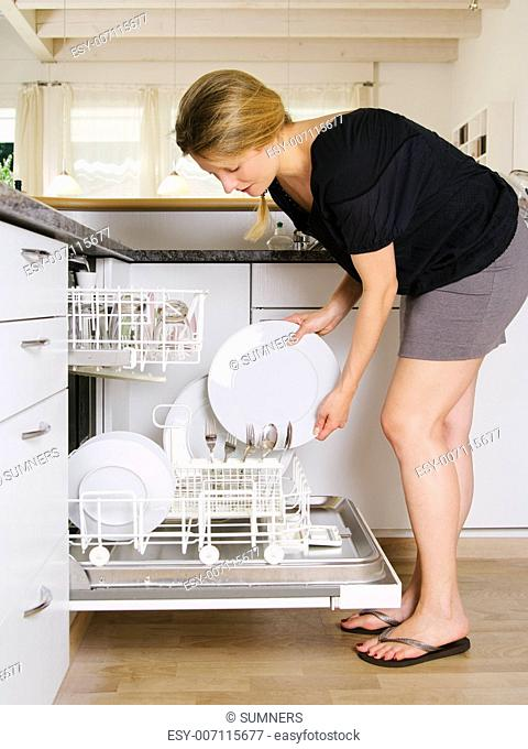 Photo of a blond female leaning over and unloading her dishwasher