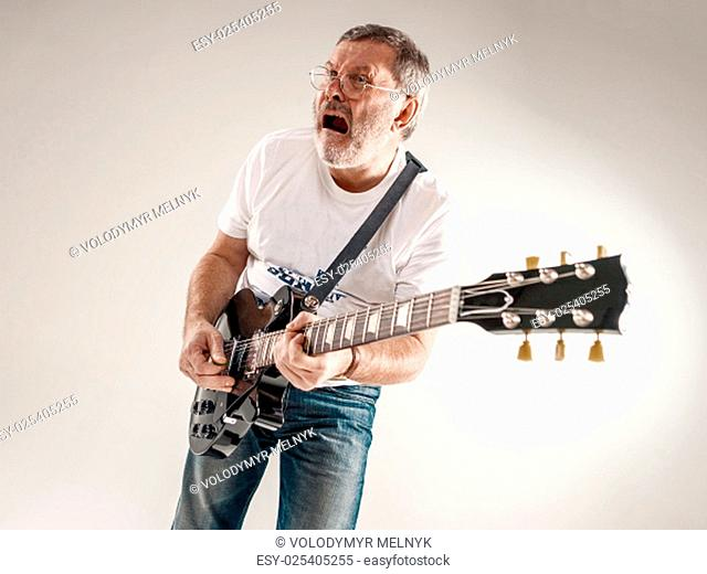 Portrait of a guitar player exciting music on gray background
