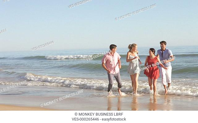 Group of friends running up beach towards camera.Shot on Canon 5d Mk2 with a frame rate of 30fps