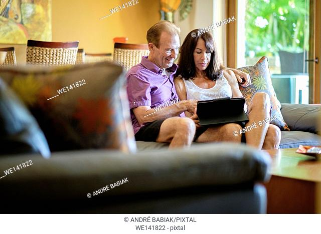 Senior man and woman sitting on the couch in the livingroom of their upscale home using a tablet computer