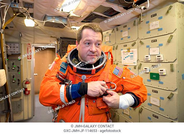 Astronaut Nicholas Patrick, STS-130 mission specialist, dons a training version of his shuttle launch and entry suit in preparation for a training session in...