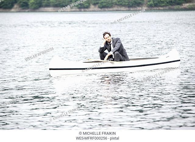 Germany, Rur Reservoir, businessman relaxing in canoe
