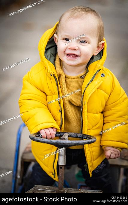 Baby boy of one year old driving a play toy cart and having fun