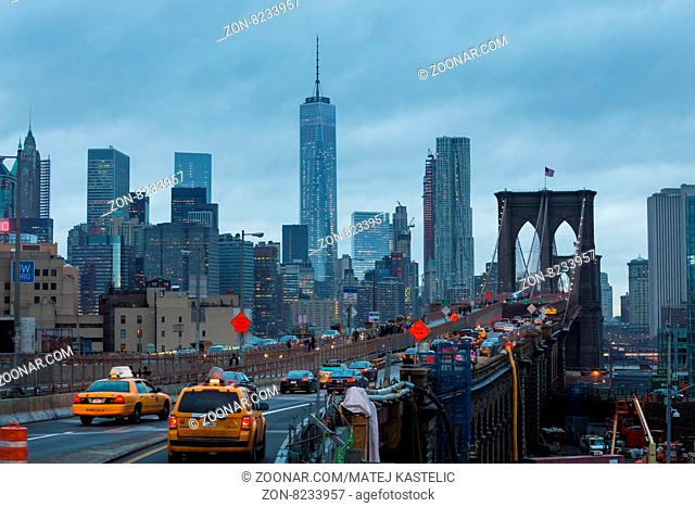 New York City, United States of America - March 25: Traffic on Brooklyn bridge and New York City Manhattan downtown skyline at dusk with skyscrapers over East...