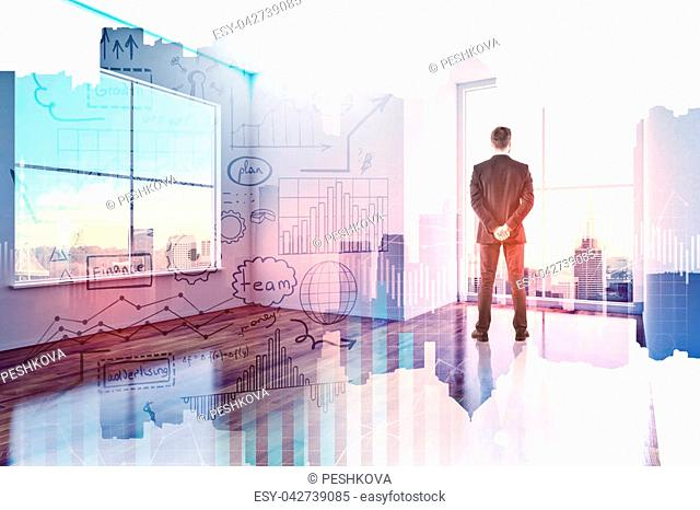 Businessman in modern office interior with abstract business sketch hologram. Success and marketing concept. Double exposure