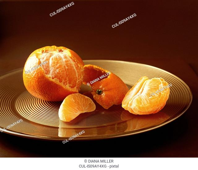 Food, fruit, clementine half peeled on golden plate