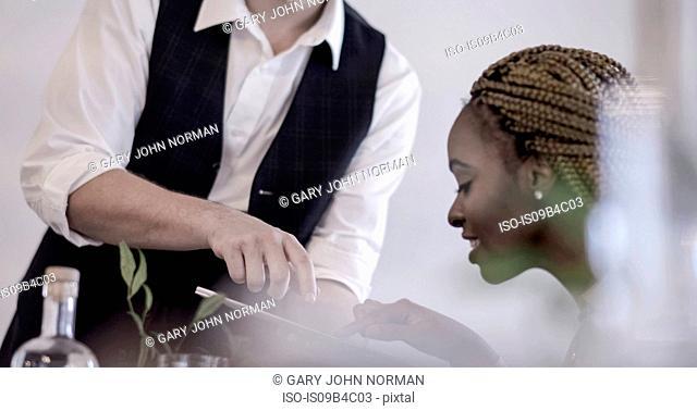 Waiter serving diner in restaurant, diner using digital tablet to pay, mid section