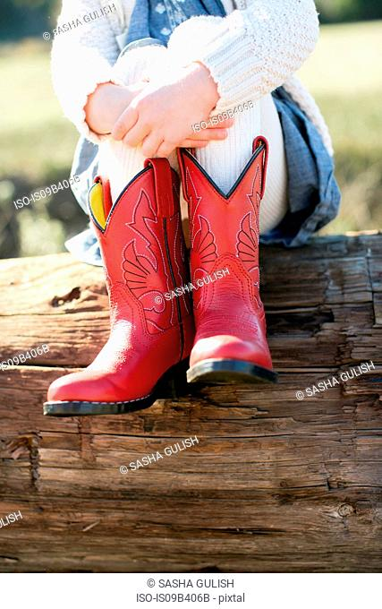 Neck down view of girl sitting on log wearing red cowboy boots