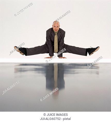 Businessman doing yoga, balancing on his hands