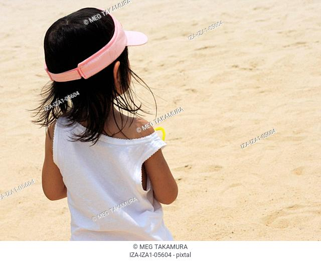 Rear view of a girl standing on the beach