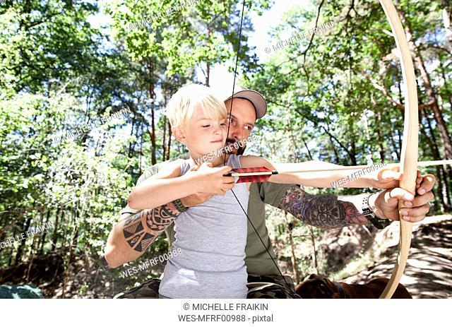 Father and son shooting with bow and arrow in the forest