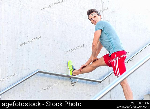 Handsome mid adult man stretching leg on wall while standing over steps