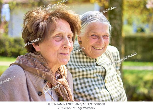 Portrait of two happy senior women together in park in Bad Wiessee, Bavaria, Germany