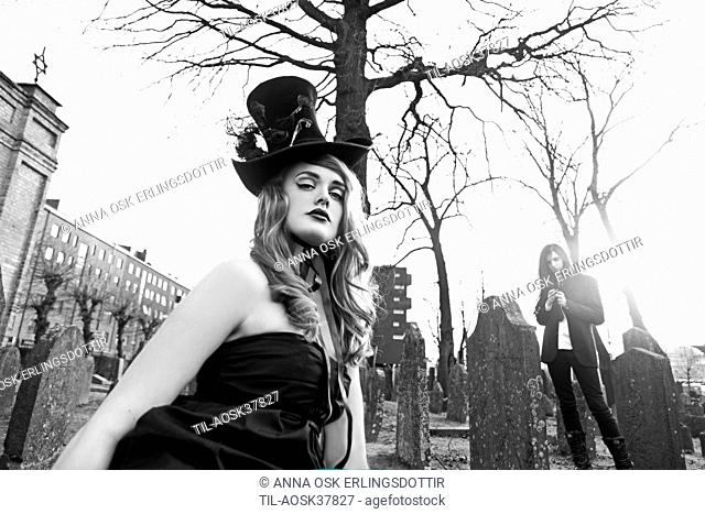 Lone female figure wearing black hat in graveyard