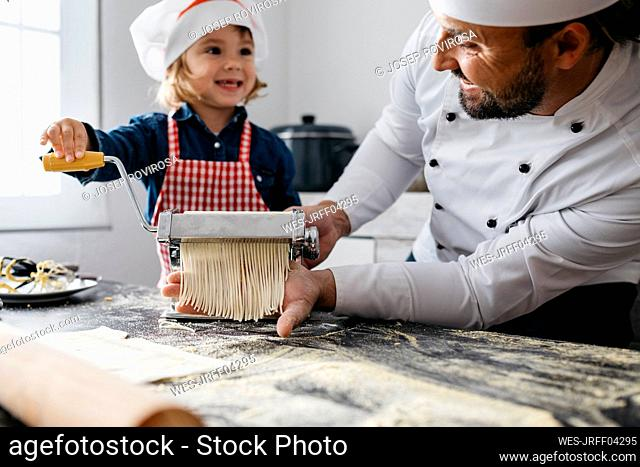 Father and daughter making homemade pasta with pasta machine in kitchen at home