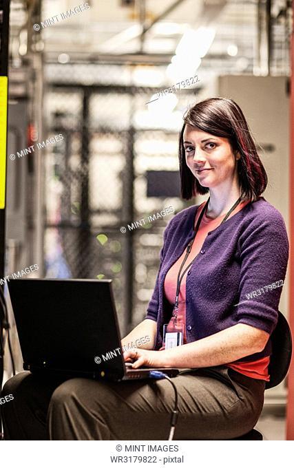 Caucasians woman technician working in a large computer server farm