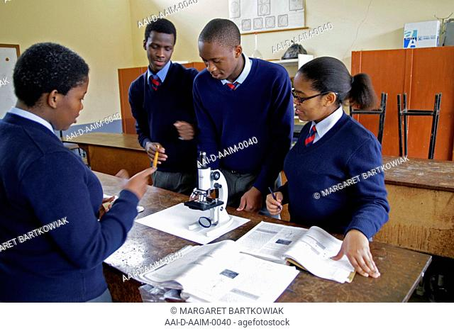 School children using microscope in school lab, St Mark's School, Mbabane, Hhohho, Kingdom of Swaziland
