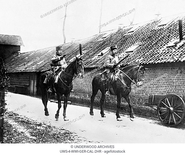 France: c. 1915 Two German calvarymen enter a French village with pistol and rifle at the ready