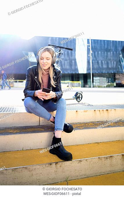 Portrait of young woman listening music with smartphone and headphones, Barcelona, Spain