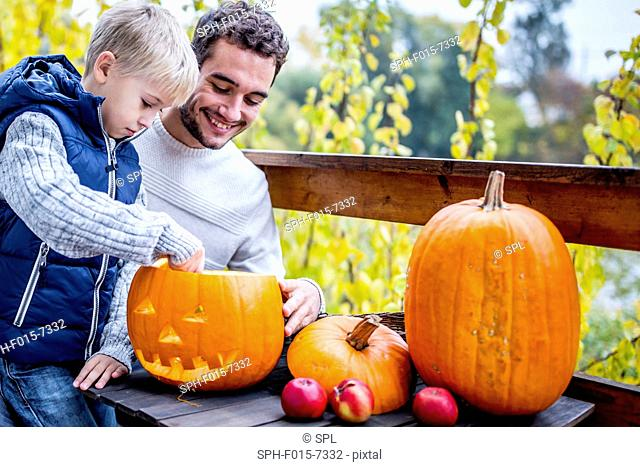 MODEL RELEASED. Father and son making Halloween pumpkin