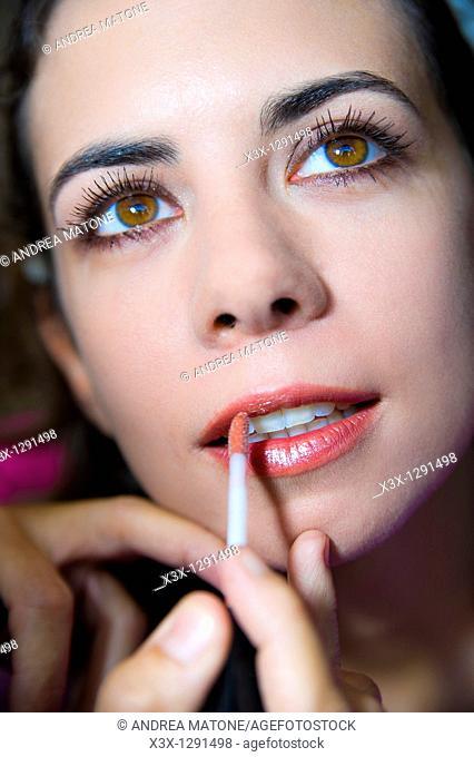Make up artist applying lip gloss on a woman